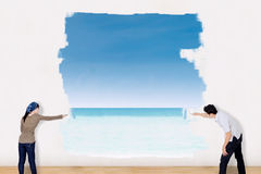 Couple painting beach landscape Stock Photo