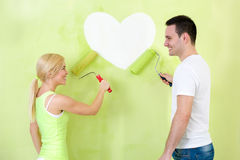 Couple painting heart on wall Royalty Free Stock Photography