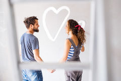 Couple painting heart on the wall in their house. Royalty Free Stock Photography