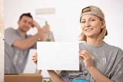 Couple painting new house. Smiling couple painting new house, woman in focus holding blank page, copyspace royalty free stock photos