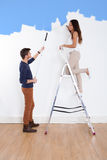 Couple Painting New House. Full length of young couple painting new house stock photo