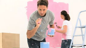 Couple painting a wall with the colour pink stock footage