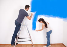 Couple painting wall at home Royalty Free Stock Image