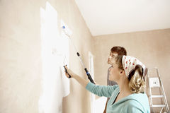 Couple Painting Wall With Paint Rollers Stock Images