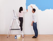 Couple painting the wall Royalty Free Stock Images