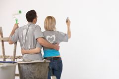 Couple painting on white wall Stock Photography