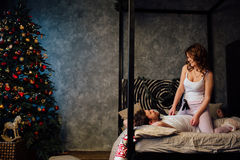 Couple in in pajamas resting on the bed near the Christmas tree. Stock Photos