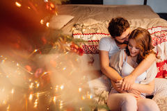 Couple in in pajamas resting on the floor next to the bed near the Christmas tree. stock photography
