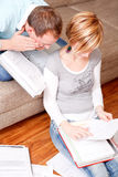Couple paper document. Scenic young family couple at home indoors in living room doing paperwork sitting on couch and floor with lot of paper documents Royalty Free Stock Image