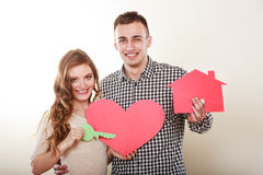 Couple with paper house and heart love symbol. Smiling young couple holding paper house key and heart sign love symbol. Husband and wife dreaming about new home stock photos