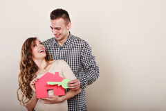 Couple with paper house. Housing real estate. Stock Photos