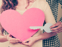 Couple with paper key to heart love symbol. stock photo