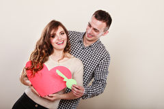 Couple with paper key to heart love symbol. Smiling young couple holding paper key to unlock heart sign love symbol. Loving husband and wife stock image