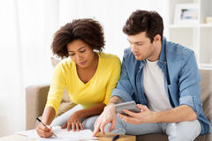 Couple with papers and calculator at home. Family budget, savings and people concept - couple with papers and calculator at home Royalty Free Stock Photography