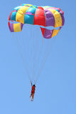 Couple with a Parachute. A young couple parasailing on a bright morning Stock Image
