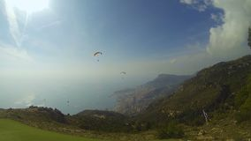 Couple of paragliders drifting over hills down towards seaside city, extreme. Stock footage stock video