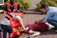 Couple of paramedics examining woman Stock Photos