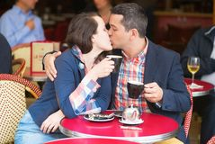 Couple in a Parisian street cafe, kissing Royalty Free Stock Image