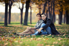 Couple in the park. Young couple sitting on the ground in the autumn park Royalty Free Stock Image