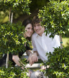 Couple in park. A smiling teenage couple sitting in a park through the trees. Focus on the trees royalty free stock photos