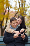 Couple on park bench. Happy couple on park bench using a smartphone Royalty Free Stock Images