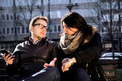 Guy holding smartphone and the girl shows on her watch. Couple on a park bench looking at each other, guy holding smartphone and the girl shows on her watch Stock Image