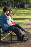 Couple on Park Bench Looking at Flower-Vertical royalty free stock photography
