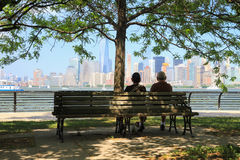 Couple in a park of Ellis Island watching the skyline of Manhatt Royalty Free Stock Photography