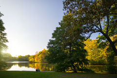 Couple in a park enjoying autumn sunset Royalty Free Stock Photography