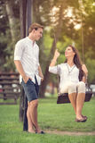 Couple in park girl on swing Stock Photography