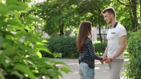 Couple in the Park holding hands and cute talk. Young couple in the Park holding hands and cute talk stock footage