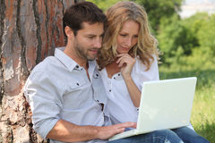 Couple in park on laptop Stock Image