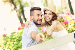 Couple in the park pointing to the camera Royalty Free Stock Photo