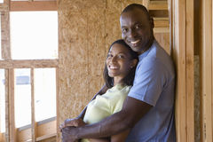 Couple in partially built house, man embracing woman, smiling, portrait Stock Photography