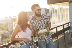 Couple at a party. Young couple having fun at a rooftop party, drinking beer, eating barbecue and chatting Royalty Free Stock Image