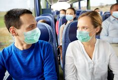 Couple of passengers in medical mask in travel bus