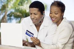 Couple on patio making online credit card purchase Royalty Free Stock Image