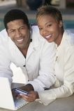 Couple on patio making online credit card purchase portrait Royalty Free Stock Photography
