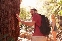 Couple Pausing By Tree Trunk In On Walk Through Forest Stock Image