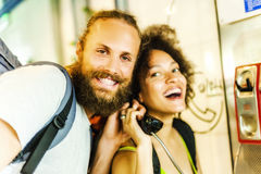 Couple on pay phone laughing Stock Photo