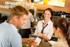 Couple paying bill at cafe cash desk. Smiling waitress bar Royalty Free Stock Photo