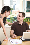 Couple paying bills by online banking. A happy couple paying bills by using online banking at home stock image