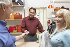Couple Paying For Clothes Through Credit Card At Counter Stock Photo