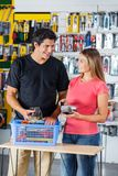 Couple Paying Through Credit Card In Hardware Royalty Free Stock Photography