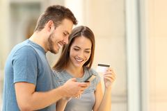 Couple paying on line with credirt card on the street. Happy couple paying on line with credirt card and smart phone on the street Stock Photos