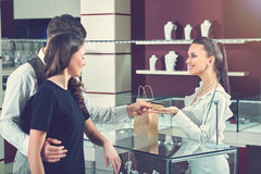 Couple paying for purchase at luxury jewelry store. Couple of brunette girlfriend and boyfriend buying jewelry and paying for purchase. Jeweler seller happy stock photos