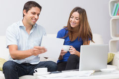 Couple paying their bills online at home Stock Images