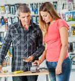 Couple Paying For Tools Through Smartphone In Royalty Free Stock Photography