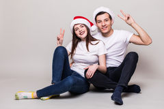 Couple with peace sign and Christmas hats Royalty Free Stock Photos