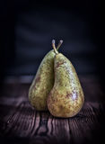 Couple pears on old rustic wooden table background, dark toned s Stock Photography